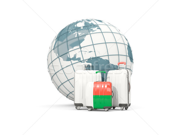 Luggage with flag of madagascar. Three bags in front of globe Stock photo © MikhailMishchenko