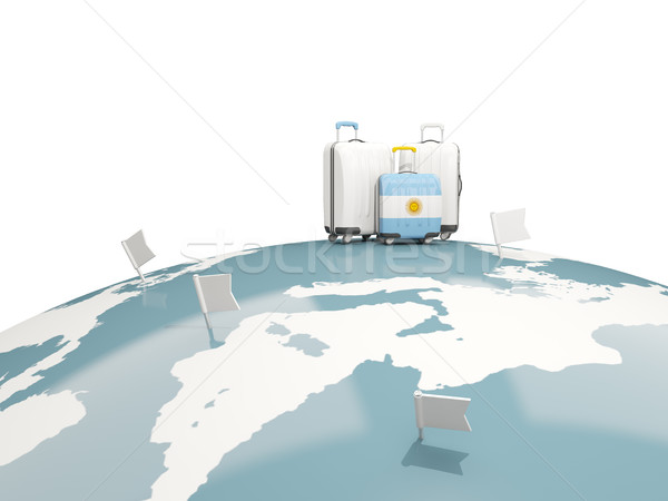 Luggage with flag of argentina. Three bags on top of globe Stock photo © MikhailMishchenko