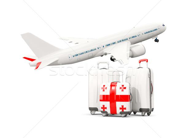 Luggage with flag of georgia. Three bags with airplane Stock photo © MikhailMishchenko