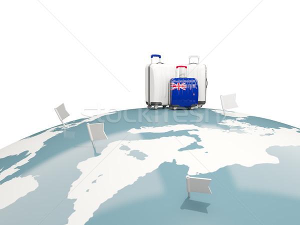 Luggage with flag of new zealand. Three bags on top of globe Stock photo © MikhailMishchenko