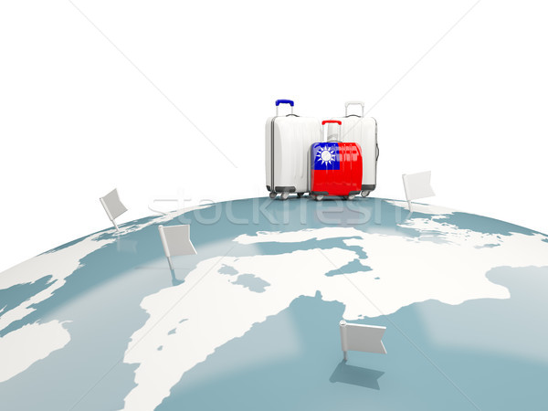 Luggage with flag of taiwan. Three bags on top of globe Stock photo © MikhailMishchenko