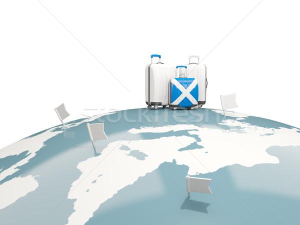 Luggage with flag of scotland. Three bags on top of globe Stock photo © MikhailMishchenko