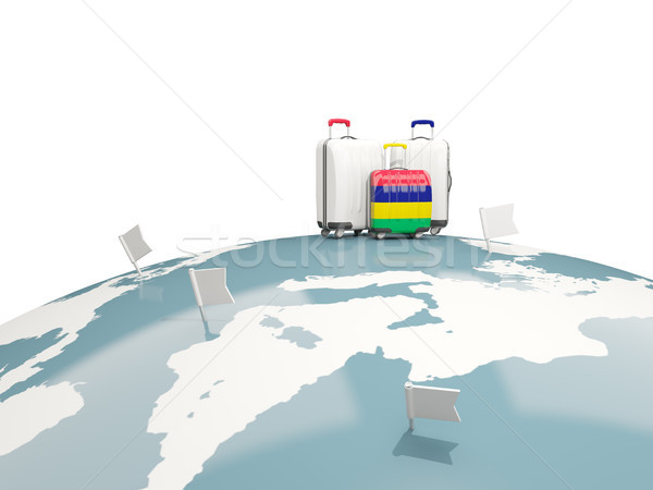Luggage with flag of mauritius. Three bags on top of globe Stock photo © MikhailMishchenko