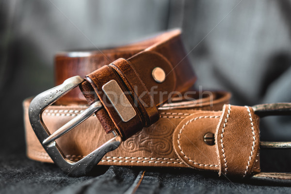 Two brown leather belts on dark background Stock photo © MikhailMishchenko