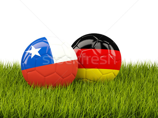 Two footballs with flags of Chile and Germany on green grass Stock photo © MikhailMishchenko