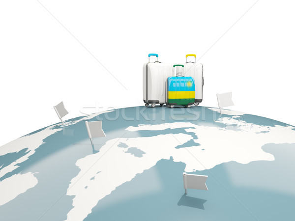 Luggage with flag of rwanda. Three bags on top of globe Stock photo © MikhailMishchenko