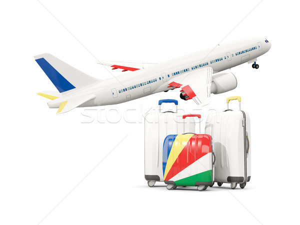 Luggage with flag of seychelles. Three bags with airplane Stock photo © MikhailMishchenko