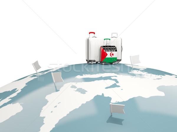 Luggage with flag of western sahara. Three bags on top of globe Stock photo © MikhailMishchenko