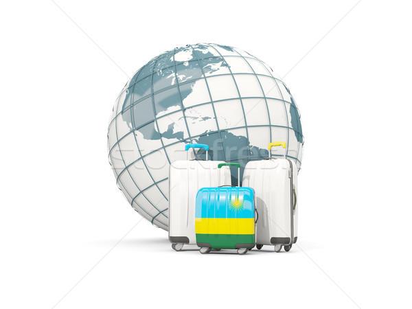 Luggage with flag of rwanda. Three bags in front of globe Stock photo © MikhailMishchenko