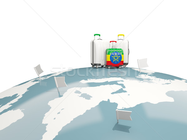 Luggage with flag of ethiopia. Three bags on top of globe Stock photo © MikhailMishchenko