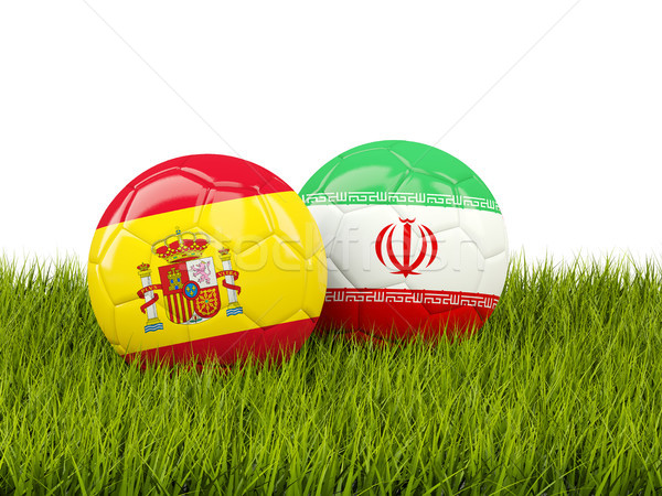 Stock photo: Spain vs Iran. Soccer concept. Footballs with flags on green gra