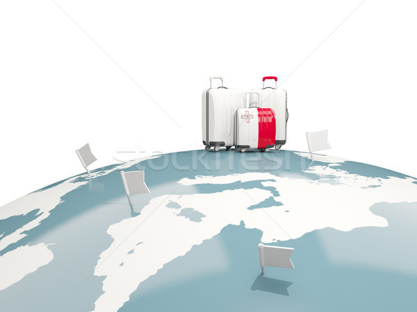 Luggage with flag of malta. Three bags on top of globe Stock photo © MikhailMishchenko