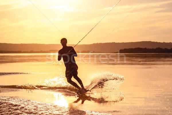 Wakeboarding. Athlete silhouette with splash of water Stock photo © MikhailMishchenko