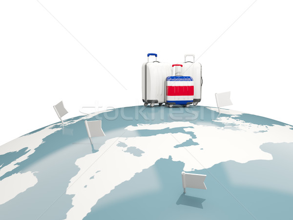 Luggage with flag of costa rica. Three bags on top of globe Stock photo © MikhailMishchenko
