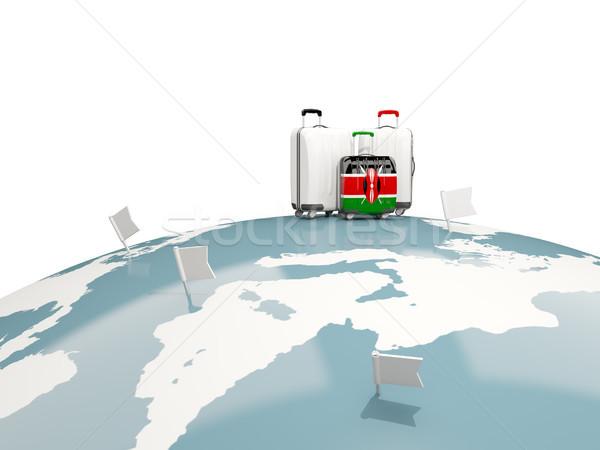 Luggage with flag of kenya. Three bags on top of globe Stock photo © MikhailMishchenko