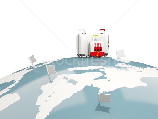 Luggage with flag of gibraltar. Three bags on top of globe Stock photo © MikhailMishchenko