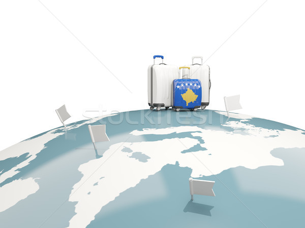 Luggage with flag of kosovo. Three bags on top of globe Stock photo © MikhailMishchenko