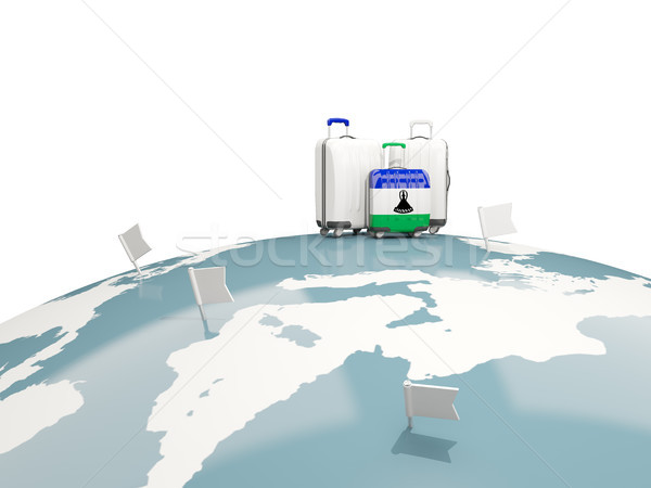 Luggage with flag of lesotho. Three bags on top of globe Stock photo © MikhailMishchenko