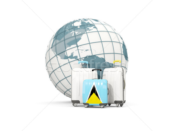 Luggage with flag of saint lucia. Three bags in front of globe Stock photo © MikhailMishchenko