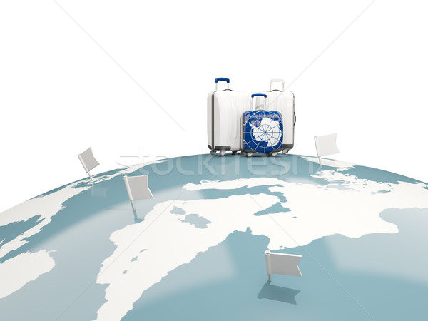Luggage with flag of antarctica. Three bags on top of globe Stock photo © MikhailMishchenko