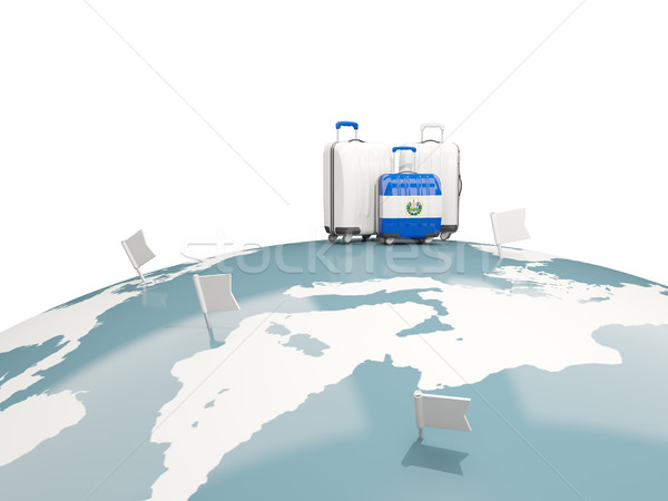 Luggage with flag of el salvador. Three bags on top of globe Stock photo © MikhailMishchenko