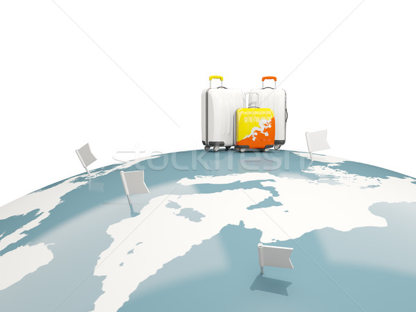 Luggage with flag of bhutan. Three bags on top of globe Stock photo © MikhailMishchenko