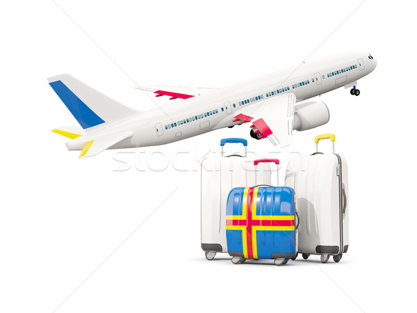 Luggage with flag of aland islands. Three bags with airplane Stock photo © MikhailMishchenko