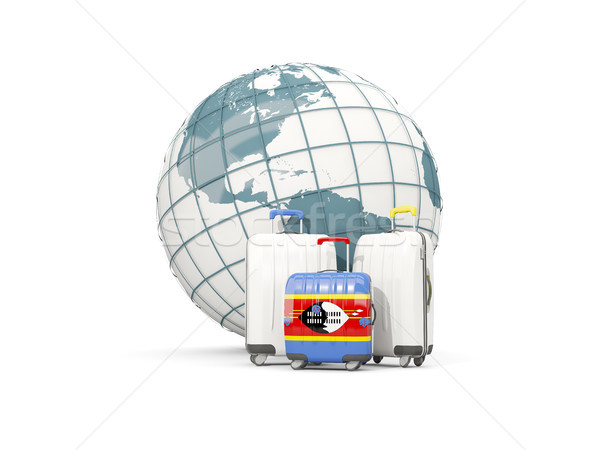 Luggage with flag of swaziland. Three bags in front of globe Stock photo © MikhailMishchenko