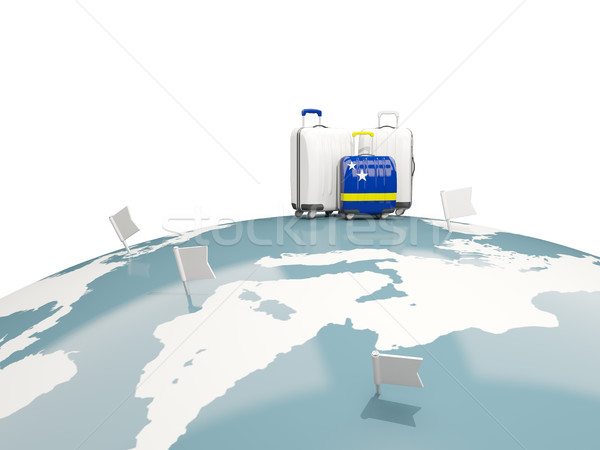 Luggage with flag of curacao. Three bags on top of globe Stock photo © MikhailMishchenko