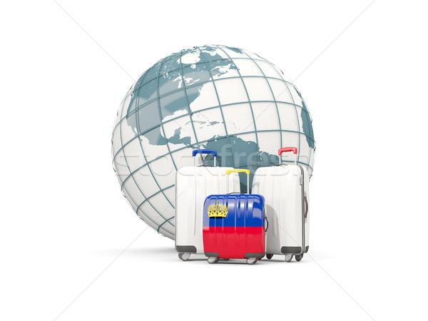 Luggage with flag of liechtenstein. Three bags in front of globe Stock photo © MikhailMishchenko