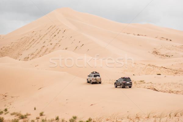 Two cars driven through sand dunes in Gobi desert Stock photo © MikhailMishchenko