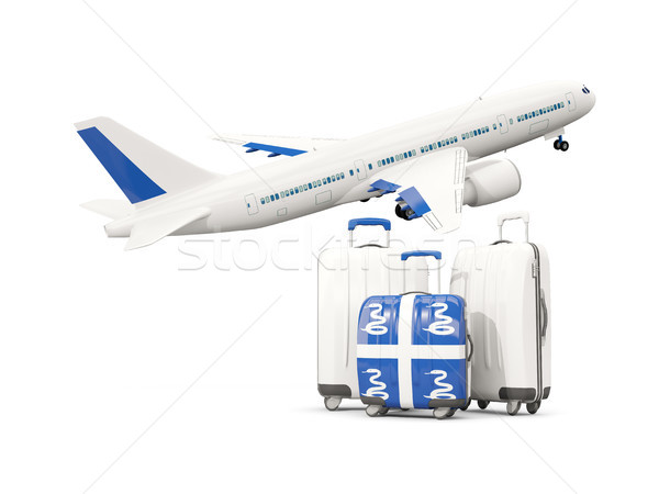 Luggage with flag of martinique. Three bags with airplane Stock photo © MikhailMishchenko