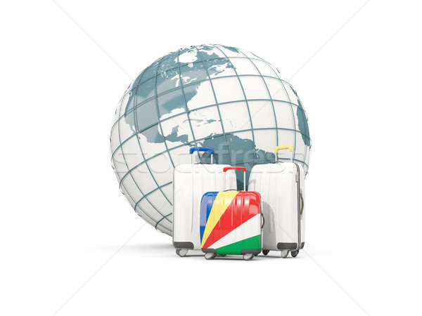 Luggage with flag of seychelles. Three bags in front of globe Stock photo © MikhailMishchenko