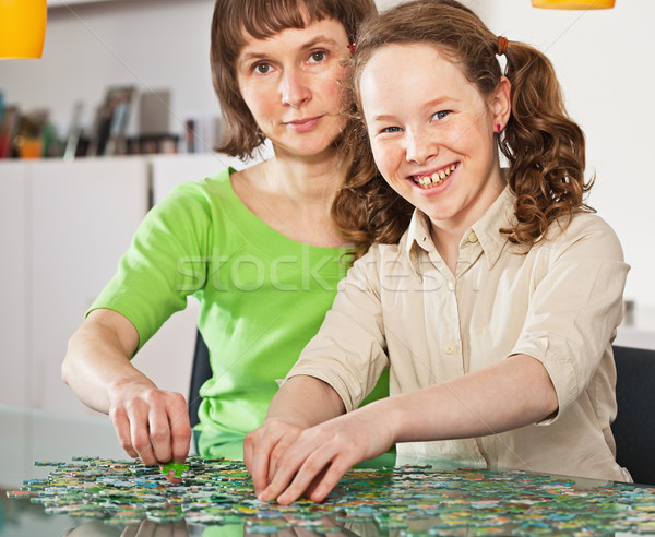 Teenager girl assembling jigsaw with her mother Stock photo © MikLav