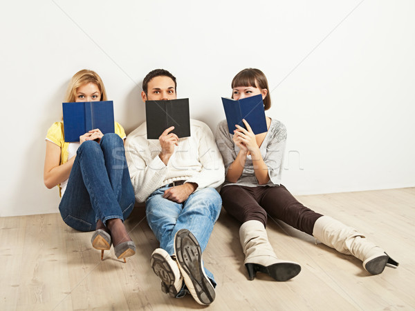 Three amused friends with books Stock photo © MikLav