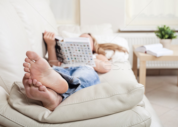 Woman on sofa with book Stock photo © MikLav