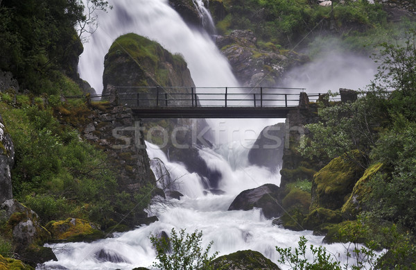 Bridge across the stream near a powerful waterfall  Stock photo © MikLav