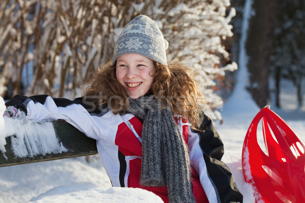 Girl in winter cloths with red sledge Stock photo © MikLav