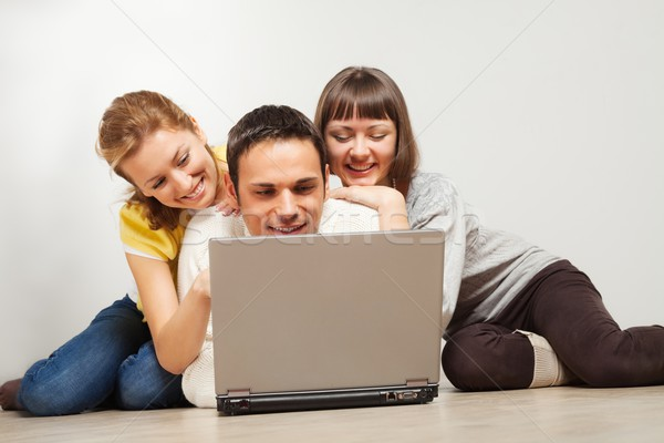 Happy friends with laptop computer Stock photo © MikLav