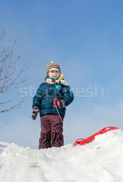 Boy standing with red plastic sledge on a snowy hill Stock photo © MikLav