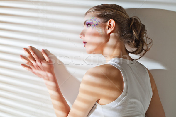 Stock photo: Woman standing by the window with blinds