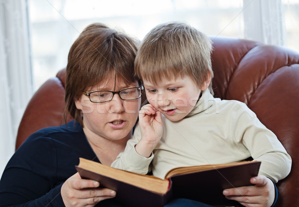 Boy and his mom reading book together Stock photo © MikLav
