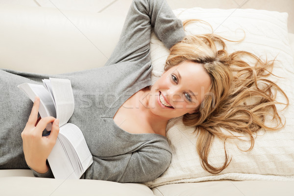 Happy young woman lying with book Stock photo © MikLav