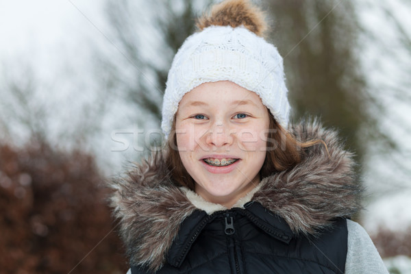 Stock photo: Smiling teenager girl in a winter park
