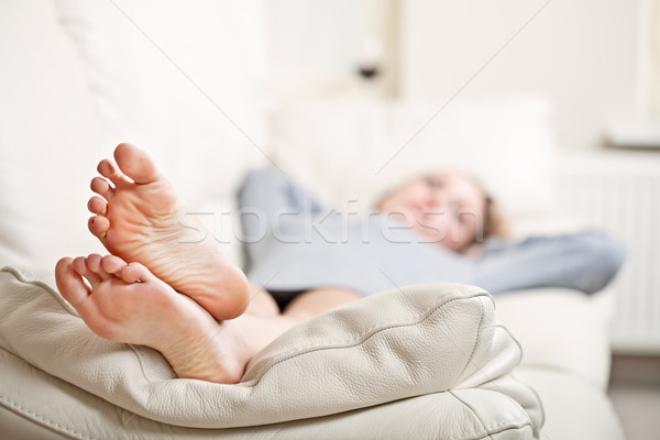 Young woman lying on sofa, focus on her feet Stock photo © MikLav