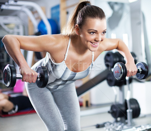 Young woman doing shoulder exercise Stock photo © MilanMarkovic78