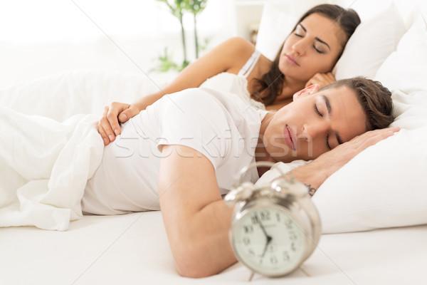 спальный пару кровать молодые гетеросексуальные пары будильник Сток-фото © MilanMarkovic78