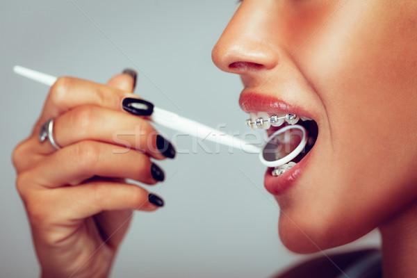Fogszabályozó közelkép mosolygó nő arc fogászati tükör Stock fotó © MilanMarkovic78