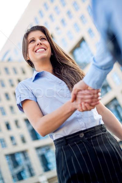 Acuerdo jóvenes mujer de negocios mano empresarial edificio Foto stock © MilanMarkovic78