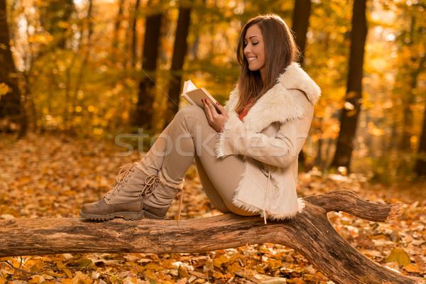 Stock fotó: élvezi · erdő · gyönyörű · fiatal · mosolygó · nő · olvas
